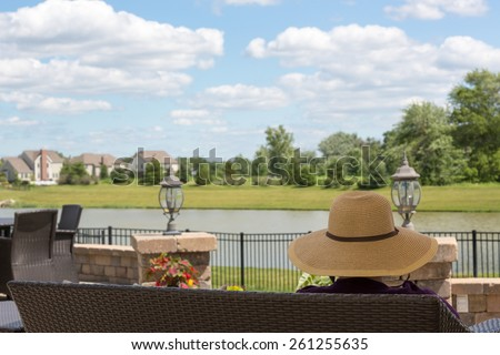 Woman in a sunhat sitting on a patio bench overlooking her garden and a tranquil lake enjoying the summer weather and pretty fluffy white clouds in a blue sky - stock photo