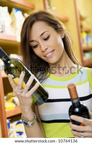 woman in a supermarket comparing two wines - stock photo