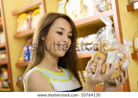 woman in a supermarket reading nutrition information and comparing two products - stock photo