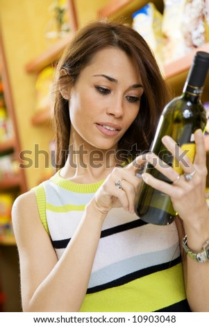 woman in a supermarket reading the label behind a bottle of wine - stock photo