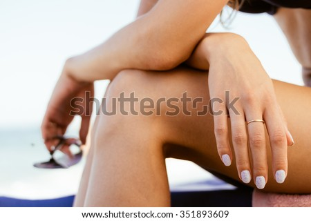 Woman in a swimsuit sits on the coast, in her hand sunglasses. Close-up. Warm colors. - stock photo