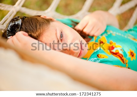 woman in a turquoise dress resting in a hammock  - stock photo