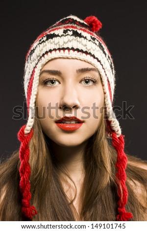 woman in a warm hat. black studio - stock photo