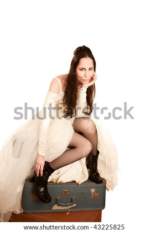 Woman in a wedding dress sitting on suitcases - stock photo