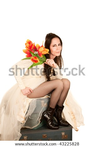 Woman in a wedding dress with plastic flowers sitting on suitcases - stock photo