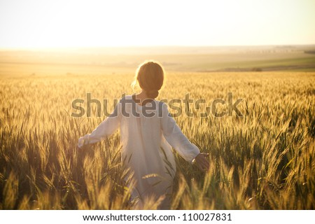 Woman in a wheat field on the background of the setting sun - stock photo