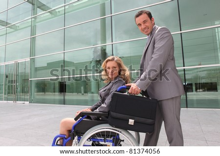woman in a wheelchair and man helping - stock photo