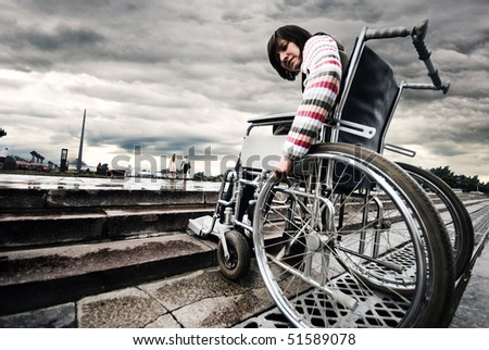 Woman in a wheelchair in front of an obstacle - stock photo