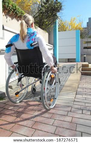Woman in a wheelchair on a wheelchair ramp - stock photo
