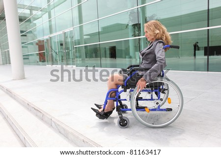 Woman in a wheelchair outside an office building - stock photo
