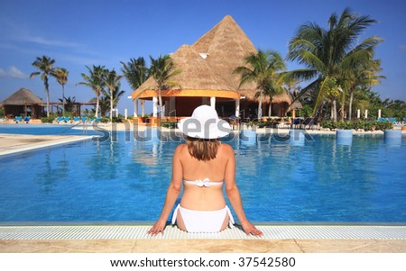 Woman in a white bikini relaxing by the swimming pool of a beach tourist resort