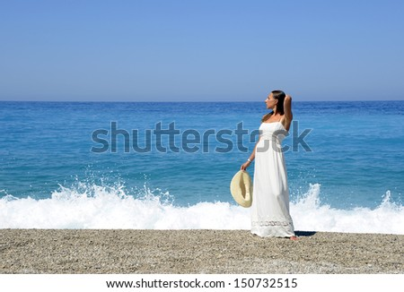 Woman in a white dress on the sea shore - stock photo