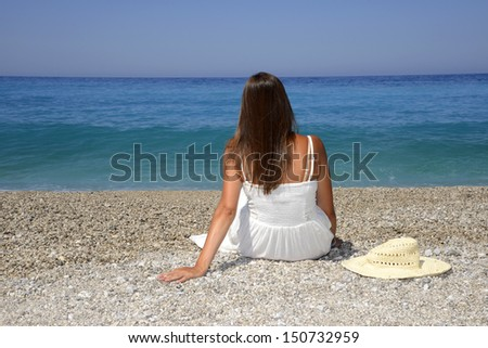 Woman in a white dress sits near the sea - stock photo