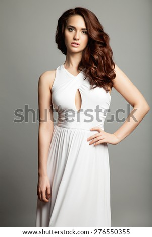 Woman in a white dress with a long thick curly hair on gray background - stock photo