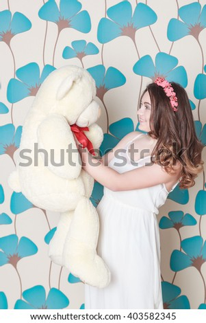 woman in a white dress with a white bear - stock photo