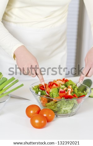Woman in a white kitchen making a healthy salad with vegetables.