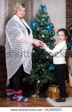 Woman in a white shawl decorating the fir-tree with little girl - stock photo