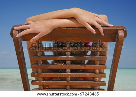 Woman in a wooden chair looking out at the sea on a beach in Mexico. - stock photo
