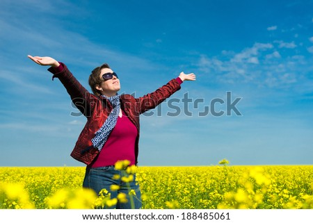 woman in a yellow field of rapeseed - stock photo