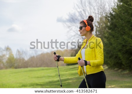 Woman in a yellow jacket and black leggings practicing Nordic walking. Listening to her favorite music.