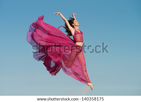 Woman in airy crimson dress jumping in the air, blue sky background - stock photo
