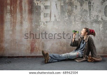 Woman in alternative clothes drinking a beer on a city street - stock photo