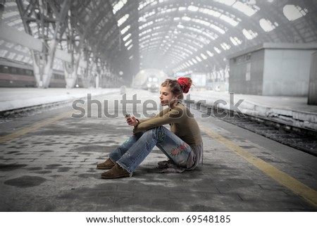 Woman in alternative clothes using a mobile phone in a train station - stock photo
