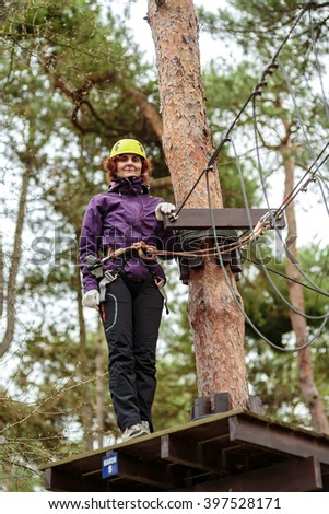 Woman in an adventure park wearing protective gear - stock photo