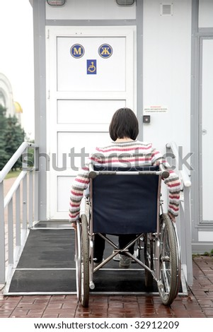 woman in an invalid carriage tries to move down in a toilet for invalids - stock photo