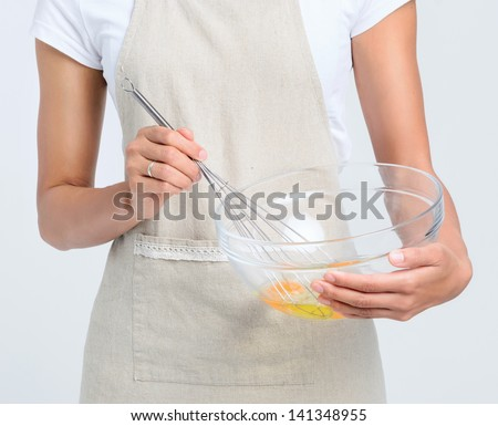 Woman in apron eating eggs in a glass bowl - stock photo