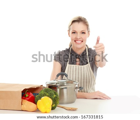 Woman in apron sitting on the desk with grocery bagand showing ok , isolated on white background - stock photo