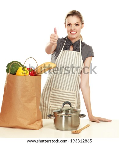 Woman in apron standing on the desk with grocery bagand showing ok , isolated on white background - stock photo