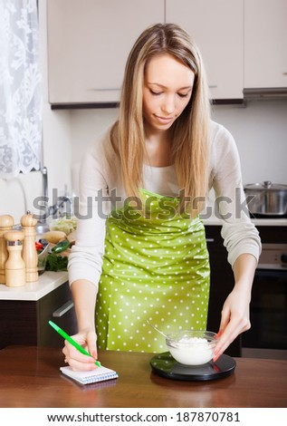 woman in apron weighing cottage cheese on kitchen scales