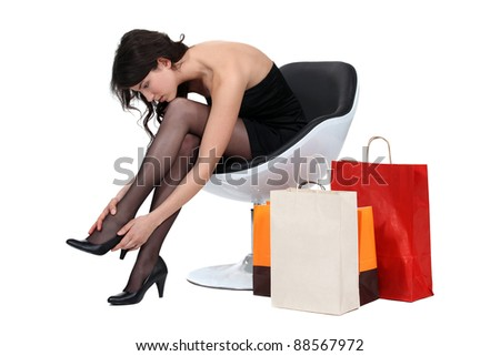 Woman in armchair with shopping - stock photo