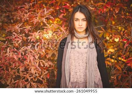 woman in autumn day near red bush - stock photo