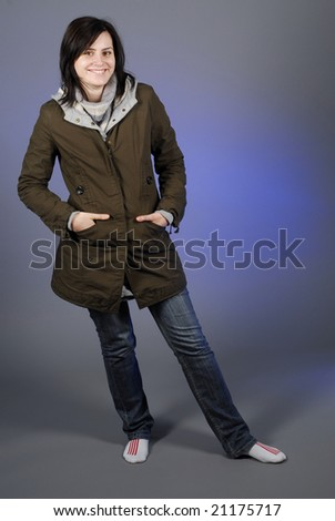 Woman in autumn/winter clothes posing in studio with no shoes - stock photo