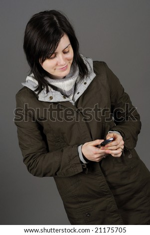 Woman in autumn/winter clothes texts a message to a friend - stock photo