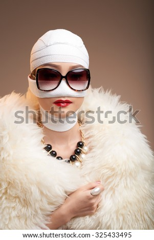 Woman in bandage wearing fur coat and jewelry - stock photo