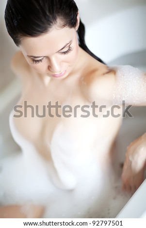 Woman in bath relaxing. Closeup of young  woman in bathtub bathing with closed eyes. - stock photo