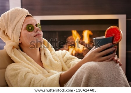 Woman in bathrobe and towel relaxing in facial mask, fruit pack, holding tea mug in front of fireplace. - stock photo