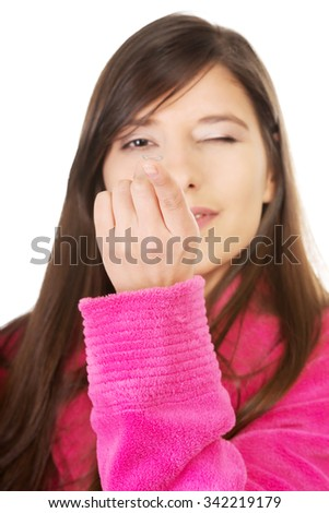 Woman in bathrobe holding contact lens.