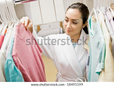 Woman in bathrobe looking in closet for clothing - stock photo
