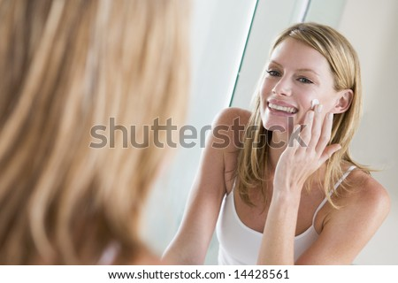 Woman in bathroom applying face cream smiling - stock photo
