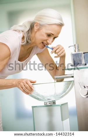 Woman in bathroom brushing teeth - stock photo