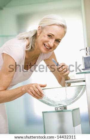 Woman in bathroom brushing teeth smiling - stock photo
