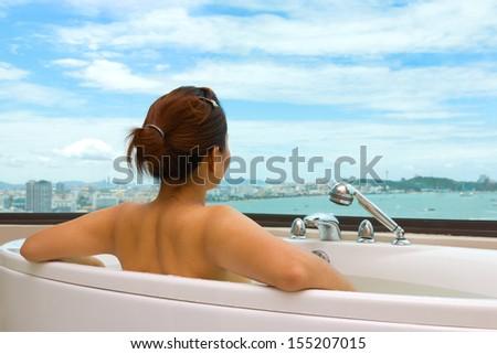 Woman in bathtub looking sea view - stock photo