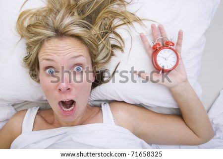 Woman in bed realizing that she has slept in despite having an alarm clock - stock photo