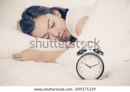Woman in bed trying to wake up with alarm clock - stock photo