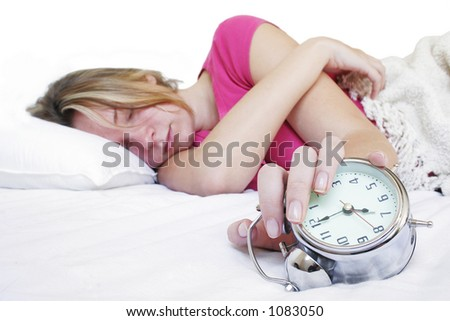 Woman in bed with alarm clock