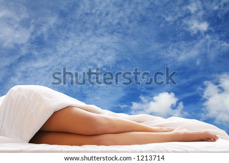 Woman in bed with blue sky showing through the window behind
